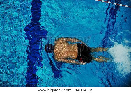 start position race concept with fit swimmer on swimming pool