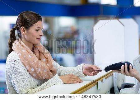 Customer making payment through payment terminal in pharmacy