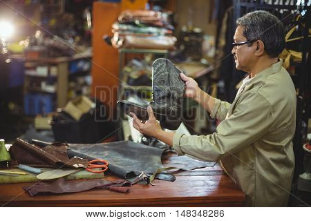 Shoemaker examining a leather boot in workshop