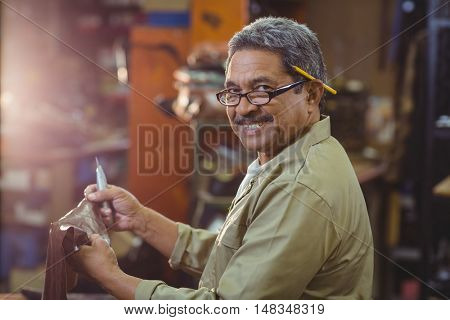Portrait of smiling shoemaker cutting a piece of leather in workshop