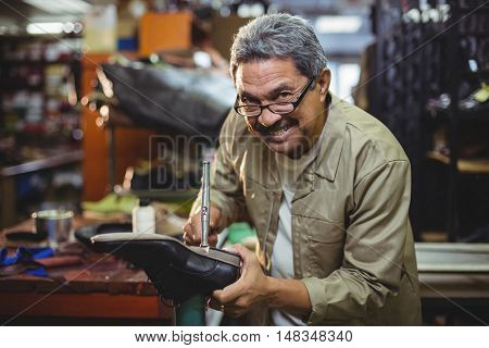 Portrait of smiling shoemaker hammering on a shoe in workshop