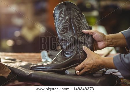 Shoemaker holding a leather boot in workshop