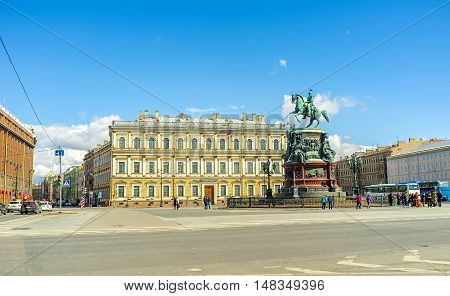 SAINT PETERSBURG RUSSIA - APRIL 25 2015: The monument of Tsar Nicholas I located in St Isaac's Square with the neoclassical building of Vavilov Institute of Plant Industry on the background on April 25 in Saint Petersburg.
