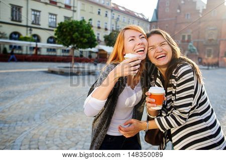 Two cute girlfriends stood in the empty cozy square European city. Girls are holding paper cups with coffee. Communication brings joy. In the background beautiful architecture.
