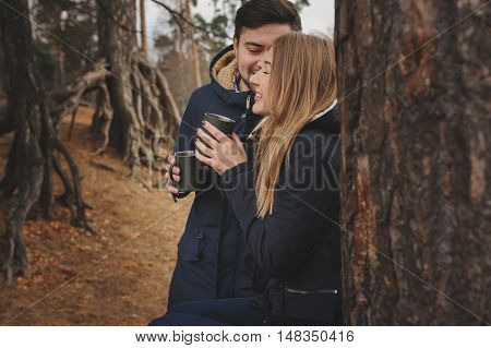 lifestyle capture of happy couple drinking hot tea outdoor on cozy warm walk in forest poster