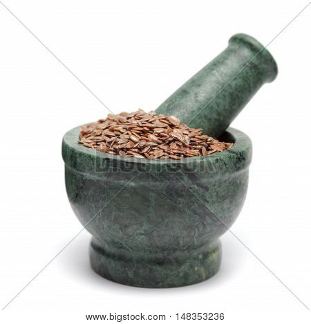 Organic Linseed or Flaxseed (Linum usitatissimum) on marble pestle. Isolated on white background.