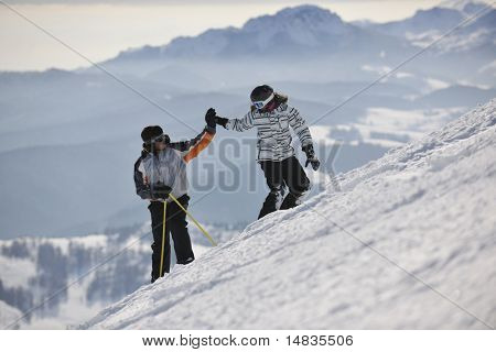 happy couple driving and relaxing with snowboard and ski at winter seasson on mountain