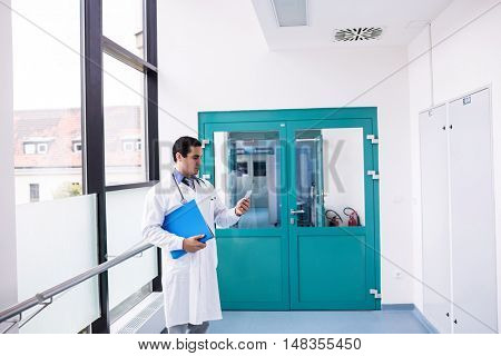 Doctor using mobile phone in hospital corridor