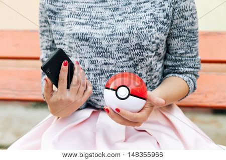 Irkutsk, Russia - September 15, 2016: Issue 2016 Image: Fan Art and Pokebol Pikachu Pokemon smartphone in the hands of women. Play Pokeball - this equipment to catch Pok mon in the game Pok mon go
