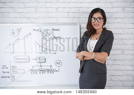 Confident smling business lady standing at whiteboard with charts
