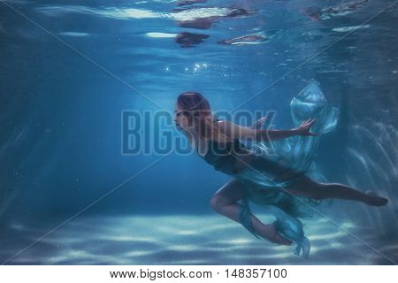 Woman in a dress dives into water fabric develops subwater.