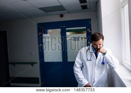 Sad doctor standing in hospital corridor