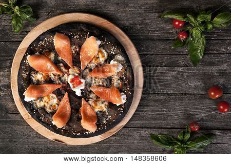 Black pizza with red fish salmon and cream cheese . Base with cuttlefish ink.