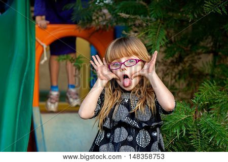 Blond girl with big blue eyes and pink glasses makes a funny face for the camera. Her hands are filthy. Her sister is ready to go down a slide in the background.