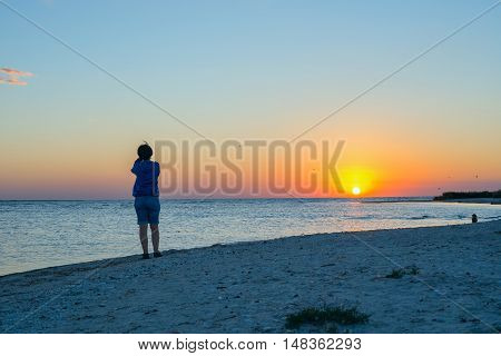 Woman photographs sunset on the beach. Back view.