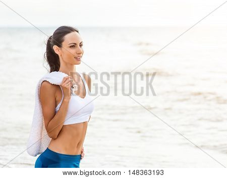 Young woman on beach listening to music in earphones from smart phone mp3 player smartphone armband Female training for marathon on beautiful beach. Mixed race Asian woman.