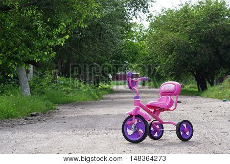 Children's bicycle standing on the empty street.
