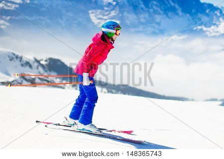 Young active woman skiing in mountains. Female skier kid with safety helmet goggles and poles enjoying sunny winter day in Swiss Alps. Ski race for adults. Winter and snow sport in alpine resort. poster