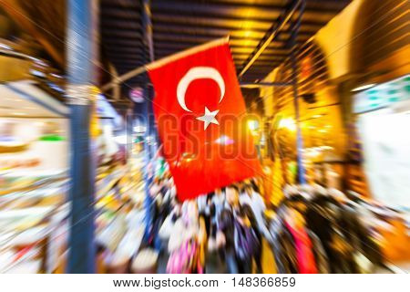 Turkish flag at Istanbul main market. Photo taken with zoom-in technique to obtain the blur effect on camera. Blurred people walking on background