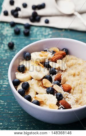 Bowl of homemade oatmeal porridge with banana, blueberries, almonds, coconut and caramel sauce on teal rustic table. Hot and diet food for breakfast.