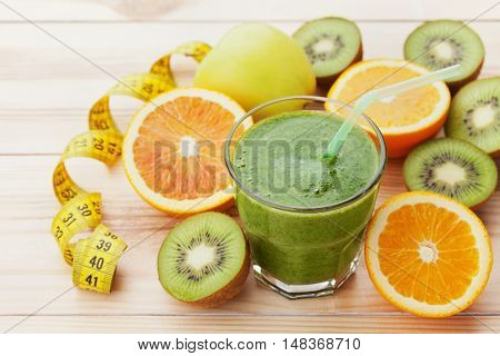 Green smoothie or juice in glass on wooden table, detox and diet food healthy breakfast.