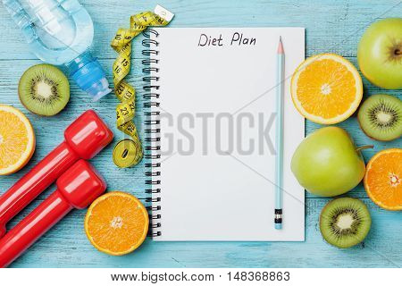 Diet plan menu or program, tape measure, water dumbbells and diet food of fresh fruits on white background. Weight loss and detox concept. Top view, flat lay.