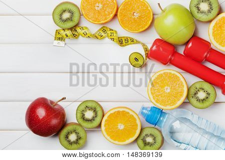 Tape measure, water dumbbells and diet food of fresh fruits on white background. Weight loss and detox concept. Top view, flat lay.