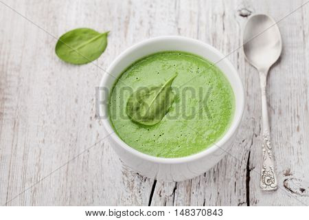 Spinach cream soup in bowl on white rustic table.