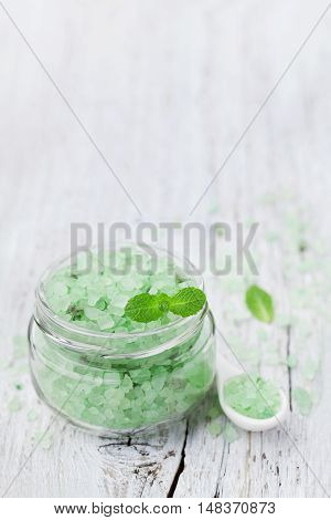 Sea salt bath scented mint for spa and aromatherapy on vintage white wooden background, rustic style.