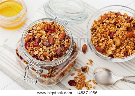 Homemade granola in jar isolated on white. Healthy breakfast of oatmeal muesli, nuts, seeds and dried fruit.