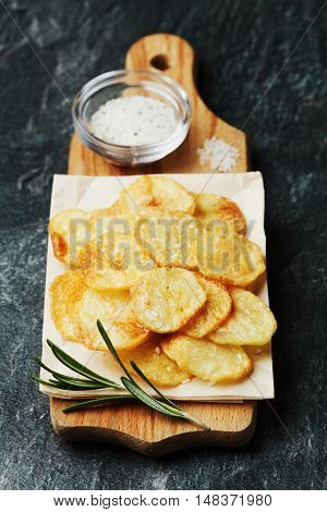 Homemade potato chips with sea salt and herb rosemary on wooden cutting board, top view.