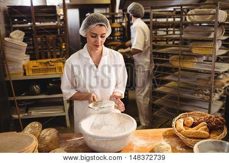 Female baker sifting flour through a sieve in bakery shop