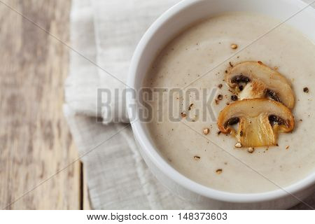 Cream soup with mushrooms champignon and potato in white bowl, vintage style.