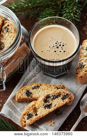 Coffee with biscotti or cantucci on wooden vintage table decorated fir tree for christmas. Traditional Italian biscuit or cookie.