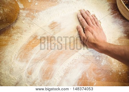 Hand of baker rubbing flour on the table at bakery shop
