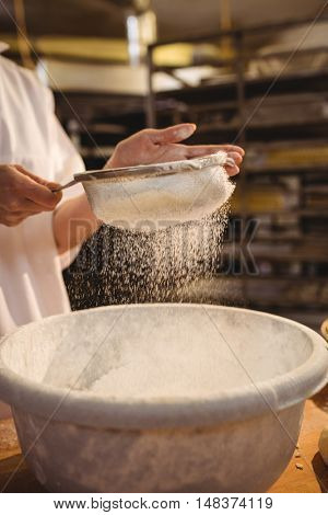 Mid-section of female baker sifting flour through a sieve in bakery shop