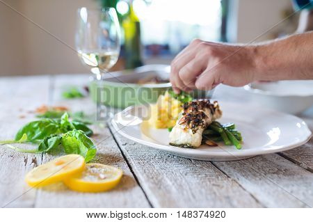 Unrecognizable man serving zander fish fillets on a plate laid on white wooden table
