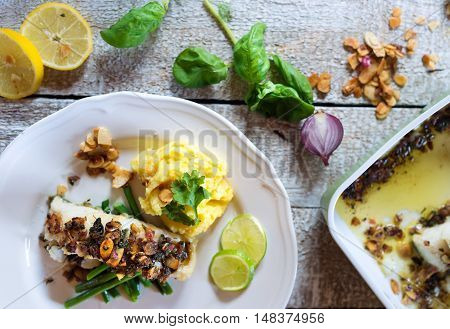 Zander fish fillet dish on a plate on white wooden table
