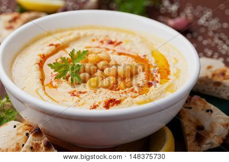 Hummus or houmous appetizer made of mashed chickpeas with tahini, lemon, garlic, olive oil, parsley and paprika.