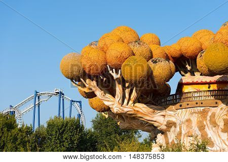 CASTELNUOVO DEL GARDA VERONA ITALY - AUGUST 28 2016: Theme park of Gardaland with the tree house of Prezzemolo (Parsley) and the Blue Tornado a roller coaster (inverted coaster)