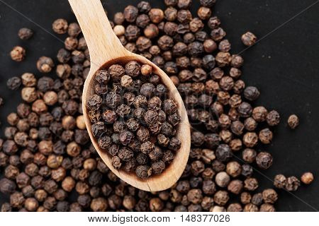 Closeup black pepper whole in wooden spoon on black stone table, top view.