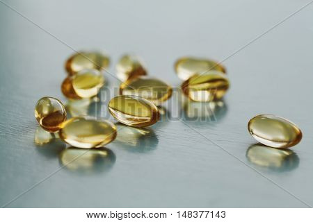 Yellow capsule with vitamin E tocopherol on blue surface, selective focus.