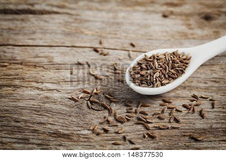 Cumin seeds or caraway in white spoon on wooden board. Macro. Copy space for text.