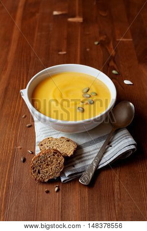 Pumpkin soup in white bowl, dietary vegetable soup. Rustic style.