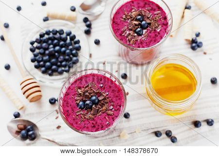 Fresh berry smoothie, milkshake or yogurt dessert, decorated grated chocolate, honey and blueberry on a white surface. Top view.