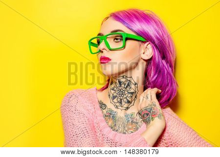 Attractive young woman with crimson hair wearing bright green glasses posing over yellow background. Bright style, fashion. Optics style. Tattoo. Hair coloring.