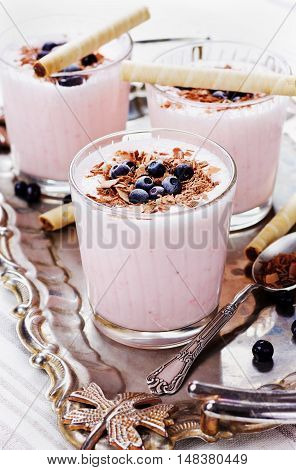 Fresh milkshake, yogurt or smoothie dessert with strawberry, decorated grated chocolate and frozen blueberries on a rustic metal tray.