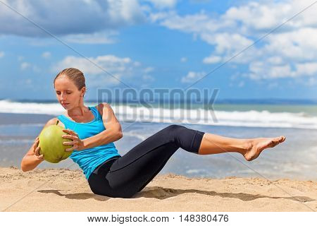 Fit woman exercising stomach muscle on ocean beach. Doing crunches core leg raising twisting exercises with coconut weight. Sportive woman doing abs workout. Fitness woman summer vacation sport camp