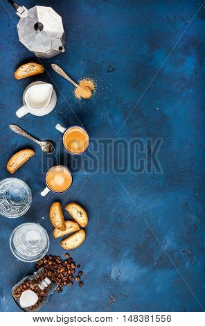 Coffee espresso in cups with italian cantucci, cookies and milk in jug over dark blue painted plywood background, top view, copy space. Food frame concept