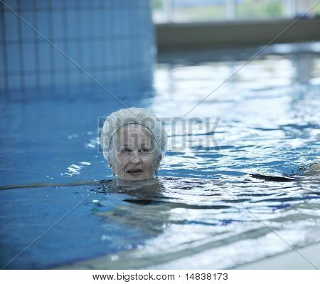 beautiful old senior  woman have fun and recreation on swimming pool